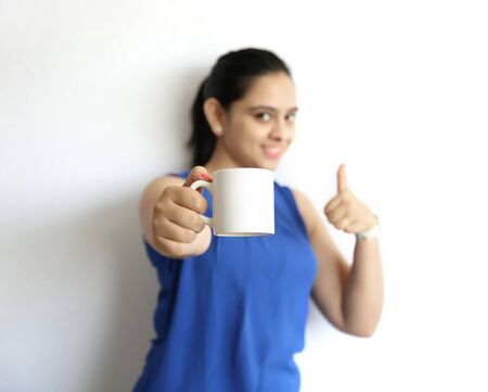 thumps up: A young beautiful indian woman holding cup of tea or coffee with thumps up, isolated on white background.