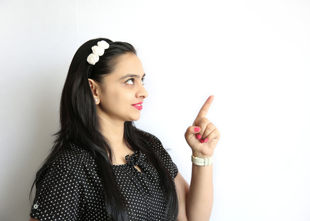 woman pointing up: A young attractive Indian girl pointing her finger isolated on a white background Stock Photo