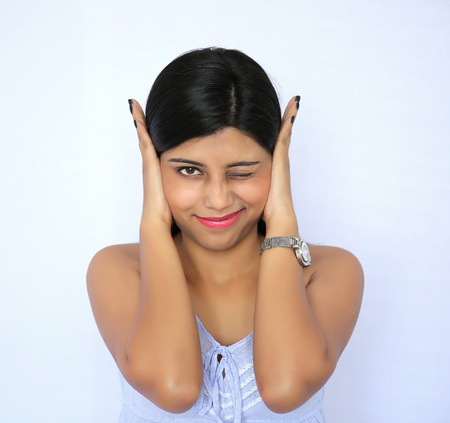 covering: Teenage indian girl covering ears with hands and keeping right eyes closed