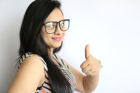 all ok: Pretty young Indian girl making thumb up gesture, shows all ok, super, isolated on a white background