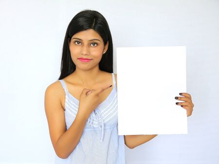 smile please: Beautiful indian woman holding a blank signboard, isolated on white background Stock Photo