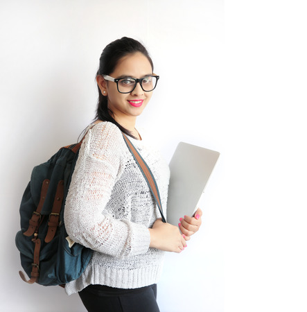 A Young Beautiful Indian College Student Holding Laptop on Isolated White Background Foto de archivo