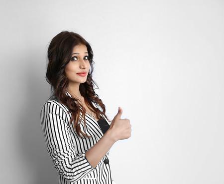 Piuttosto giovane ragazza indiana rendendo il pollice in alto gesto, mostra tutto ok, super, isolato su uno sfondo bianco