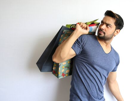 shoppingbags: A young Indian man holding shopping bags on white background.