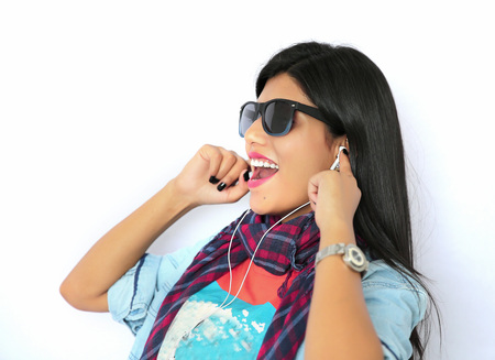 music listening: Beautiful young Indian woman listening to music with headphone and making attractive pose in sunglasses.