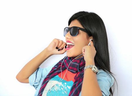 escuchando musica: Hermosa mujer india joven escuchando música con auriculares y haciendo pose atractiva en gafas de sol.