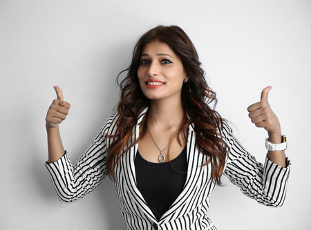 a ok: Pretty young Indian girl making thumb up gesture, shows all ok, super, isolated on a white background