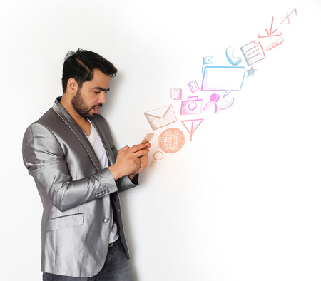 businessman phone: A handsome young Indian man checking email, chatting, internet browsing, on Mobile against a white background Stock Photo