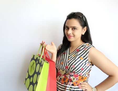 Beauty Indian Woman holding shopping bags on white background. Stock Photo
