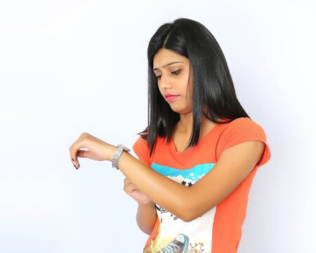 watch over: Young beautiful indian girl looks at his watch isolated over a white background Stock Photo