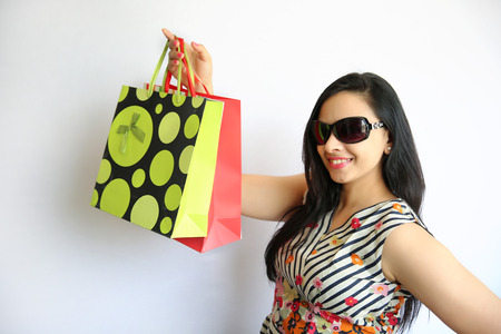 dolly bag: Beautiful Indian Woman holding shopping bags on white background. Stock Photo