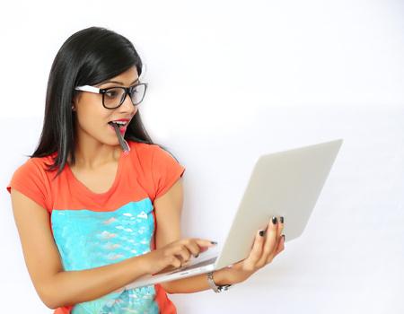 Een mooie jonge Indiase vrouw die op de laptop tegen een witte achtergrond Stockfoto