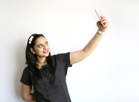 indian women: Young Indian woman take selfie of himself against the white background