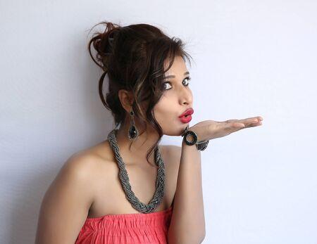 femme romantique: Vue de côté de la belle jeune femme indienne soufflant baiser sur fond blanc.