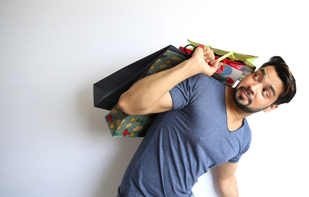 A young Indian man holding shopping bags on white background. photo