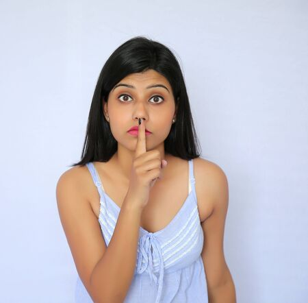woman surprise: Young Indian woman with a gesture of shh - isolated white background Stock Photo