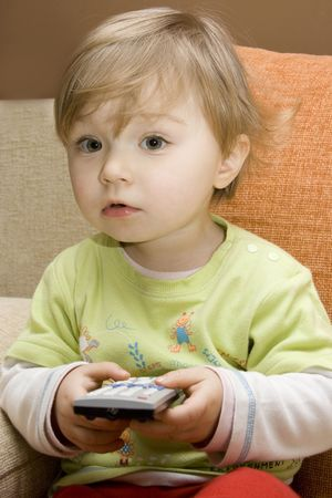 sweet baby girl with remote control on sofa Stock Photo