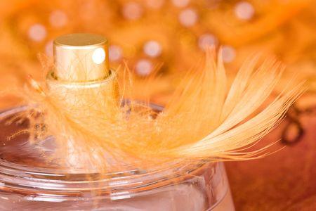 parfum: bottle of parfum with orange feather Stock Photo