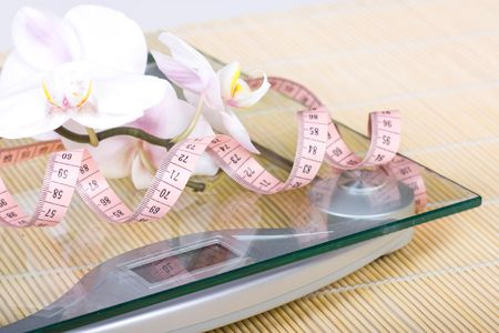 electronic scales with white orchid on matting photo