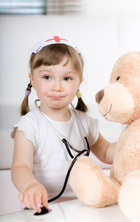 little girl doctor with teddy bear photo