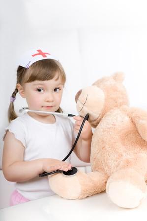 little girl doctor with teddy bear photo