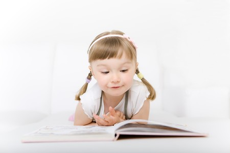 sweet happy little girl reading book Stock Photo