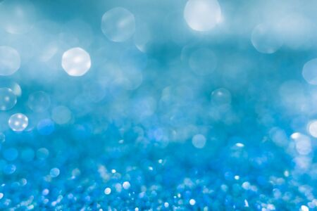 Blue sparkle glitter from diamond dust falling on the floor, blue sea water with sunlight fall over with foam. Have a lot of bokeh