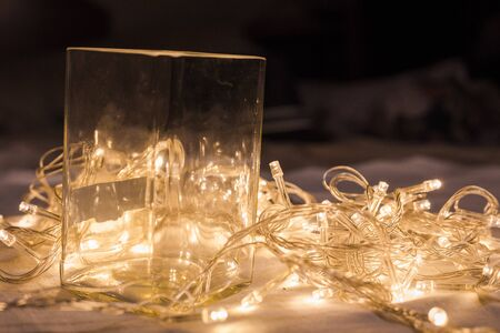 glass cup with LED light bulb wire in background Stock Photo