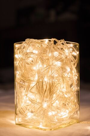 LED light bulb wire full in glass cup set on white cloth