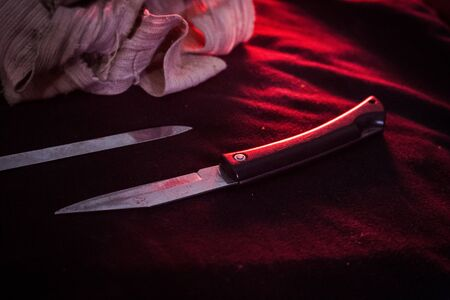 pocket knife with some bandage are on the black cloth under red light. Close up