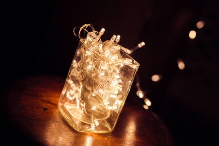 LED light bulb in glass cup on wood chair