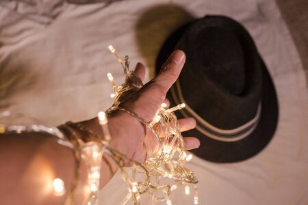 hand with LED light bulb wire lead to the fedora hat