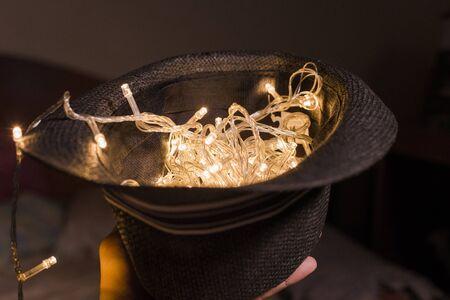hand lift fedora hat with LED light bulb full fill inside it Stock Photo