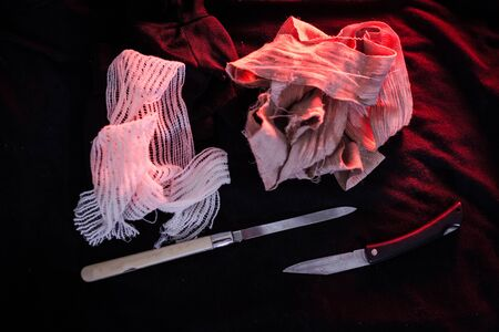 pocket knife with some bandage are on the black cloth under red light.