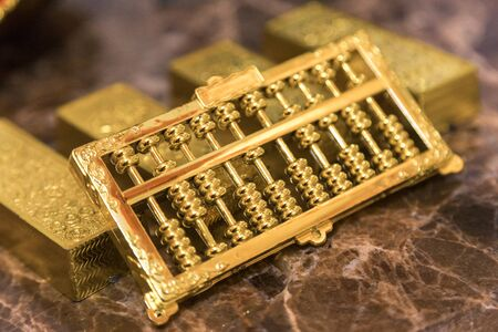 one kilo gold put on luxury marble table together in a row with golden abacus on top. closeup Stock fotó