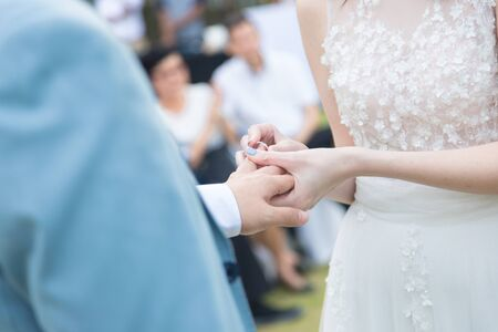 bride wearing ring to groom in wedding ceremony, lady hold man hand gently