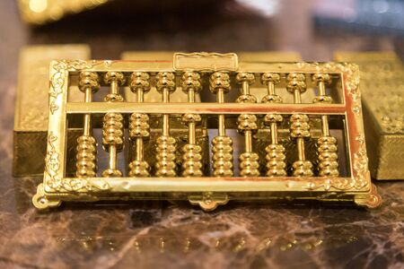 golden abacus put in front of one kilo gold, they're on luxury marble table together. closeup