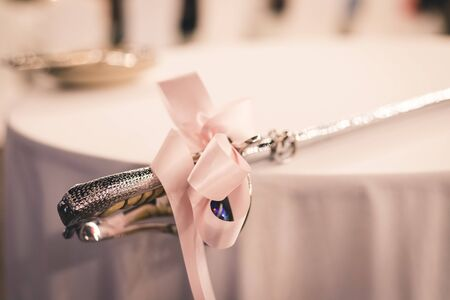 closeup of cake wedding sword handle with soft pink bow tie on it put on table prepare for cut a wedding cake Zdjęcie Seryjne