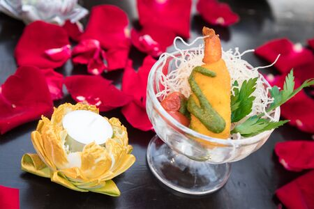 indian fried prawn balls that mix indian ingredient, decorate with some vegetable in a bowl and have red flower segment around the bowl