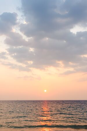 soft blue sky have some cloud with orange light color from sunset then spread to the sea - vertical
