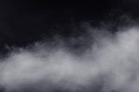 Il ghiaccio secco fumoso scende quasi al suolo con dimensioni enormi, ha un forte contrasto su sfondo nero. Muoviti sparsi nell'aria Archivio Fotografico
