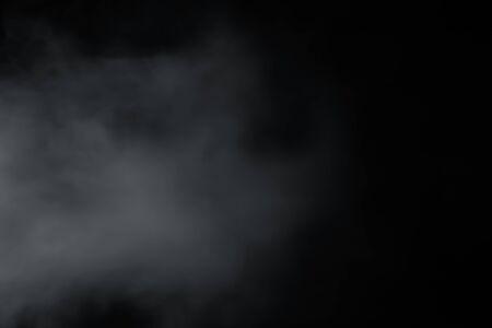 La fumée vient du côté gauche sur fond noir. Comme un doux brouillard flou