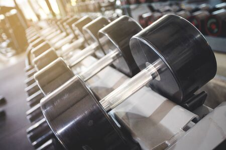 High weight Dumbbell put on the shelves in the fitness center, with some dust on it Stock Photo