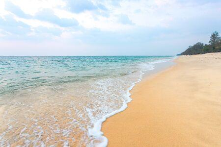 해변의 깨끗한 모래에는 바다 물결이 섬에 대각선으로 올라오고 있으며 흐린 푸른 하늘이 있습니다.