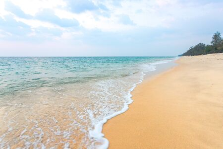 Clean sand on the beach have sea wave coming up diagonal to island, with soft blue sky with cloudy
