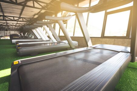 Running machine align in pattern on artificial grass with sunshine in fitness center