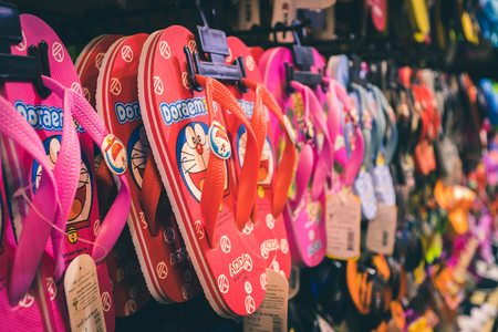Phuket, Thailand - 10 December 2018 : closeup of red one slipper with popular japanese cartoon are pattern on it, and another cartoon pattern on background 報道画像