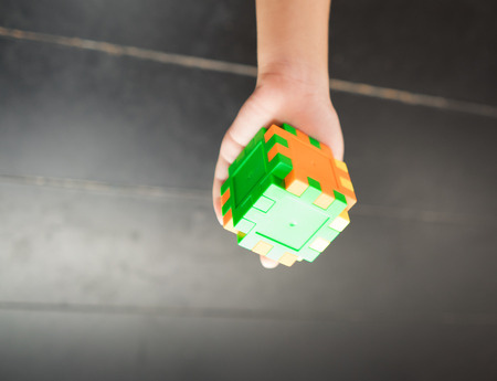 establishes: Childs hand holding colorful toy cube