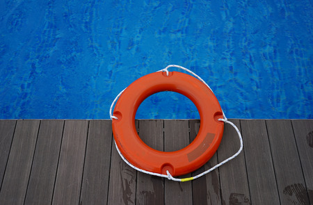 Orange life buoy on wooden deck near swimming pool