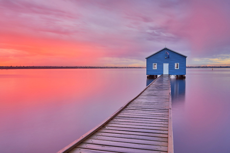 Dramatic sunrise over boathouse in the Swan River Perth, Australia